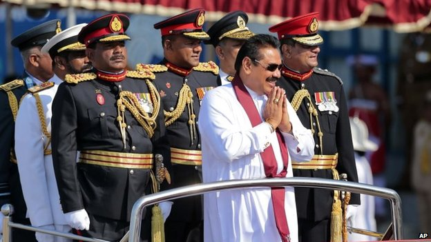 Sri Lankan President Mahinda Rajapaksa, in white, rides on a vehicle with security forces commanders as he greets people during a Victory Day parade in Matara, 18 May 2014