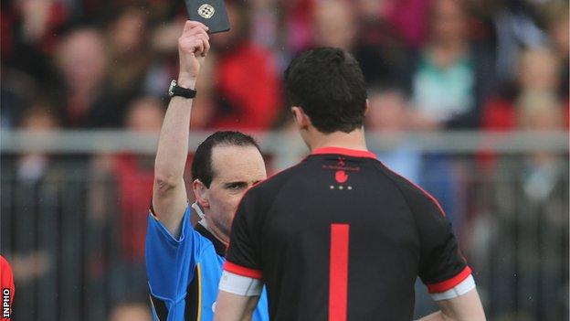 Referee David Coldrick shows a black card to Tyrone keeper Niall Morgan