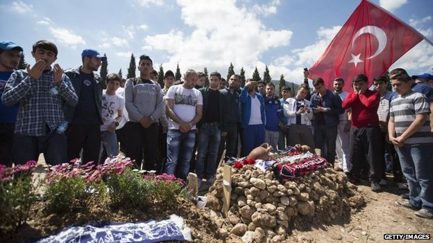 People pray in a Soma cemetery where several miners who died in the Soma mine explosion have been buried, in Soma, Turkey, 18 May 2014