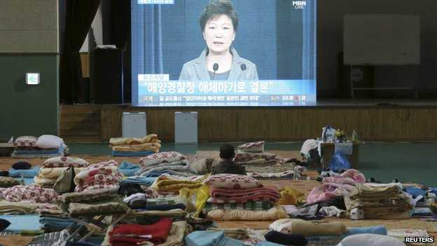 A relative of missing passengers onboard sunken ferry Sewol watches a broadcast of South Korea's President Park Geun-hye speech to the nation, at a makeshift accommodation at a gymnasium in Jindo, 19 May.