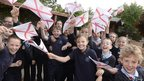 Excited, smiling children waving miniature Jersey flags