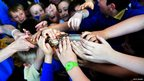 The Queen's almost obscured by a multitude of children's hands