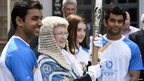 President of Tynwald Clare Christian holds the Queen's Baton flanked by young athletes