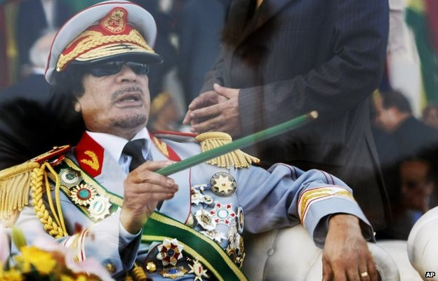 Then-Libyan leader Muammar  Gaddafi takes his seat behind bulletproof glass for a military parade in Green Square, Tripoli, Libya (September 2009)