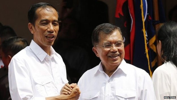 "Indonesian presidential candidate Joko ""Jokowi"" Widodo (L) and his vice presidential running mate Jusuf Kalla shake hands during an event declaring their bid in the upcoming July 9 election, in Jakarta, 19 May 2014"