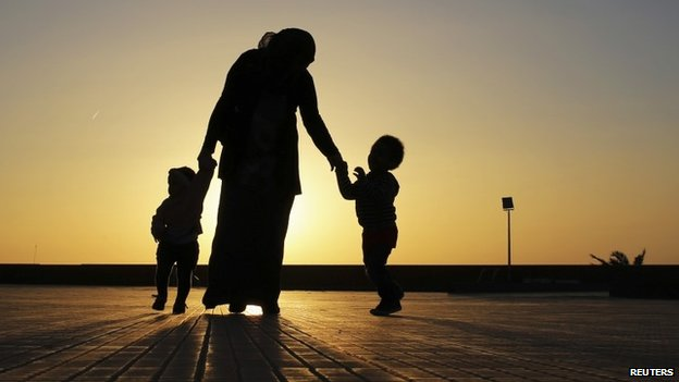 A woman walks with her two children at sunset near the seashore in Benghazi on 29 April 2014
