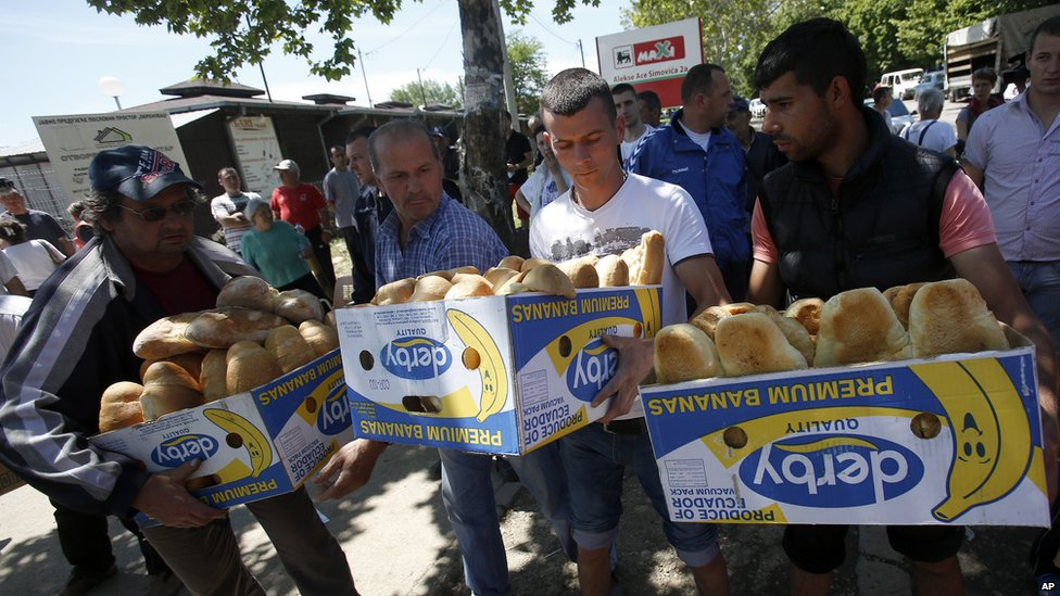 Volunteers carry food for residents in Obrenovac, Serbia