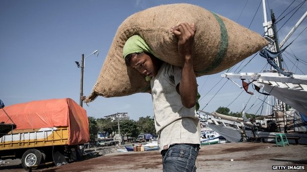 A young boy carries a sack from a boat to a lorry at the harbour in Makassar, Indonesia - 30 April 2014