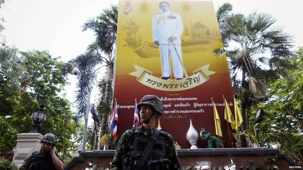 "Thai soldiers stand under a picture of Thailand""s King Bhumibol Adulyadej as they take their positions outside the headquarters of Royal Thai Police in Bangkok (20 May 2014)"