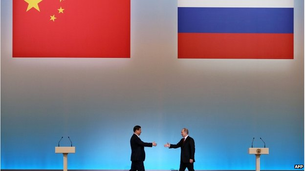 "China's President Xi Jinping (L) is welcomed by his Russian counterpart Vladimir Putin (R) during the opening ceremony of ""The Year of Chinese Tourism in Russia"" in Moscow, on 22 March, 2013"