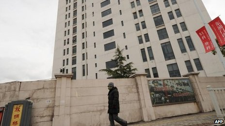 "A file picture taken on February 19, 2013 shows a person walking past a 12-storey building alleged in a report by the Internet security firm Mandiant as the home of a Chinese military-led hacking group after the firm reportedly traced a host of cyberattacks to the building in Shanghai""s northern suburb of Gaoqiao."