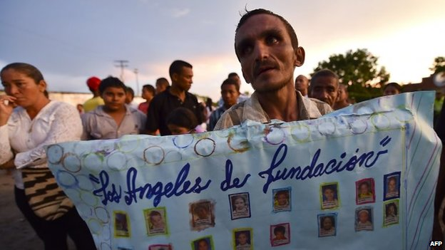 A man holds a poster with pictures of 16 of the 33 children burnt to death inside a school bus in Fundacion, at the site of the accident on 19 May, 2014
