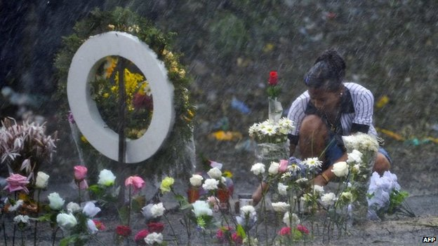 A relative lays flowers in Fundacion on 19 May, 2014