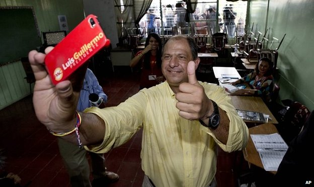 Luis Guillermo Solis, presidential candidate for the Citizen's Action Party, takes a selfie after casting his vote in the presidential runoff election in San Jose, Costa Rica