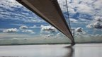 View looking up at the Humber Bridge stretching over the river Humber. Sporadic clouds dotted over a blue sky.