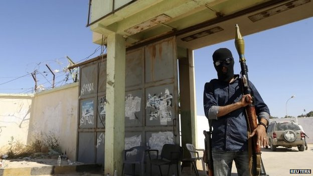 A militia stands guard in front of the entrance to the February 17 militia camp after Libyan irregular forces clashed with them in the eastern city of Benghazi May 16, 2014.