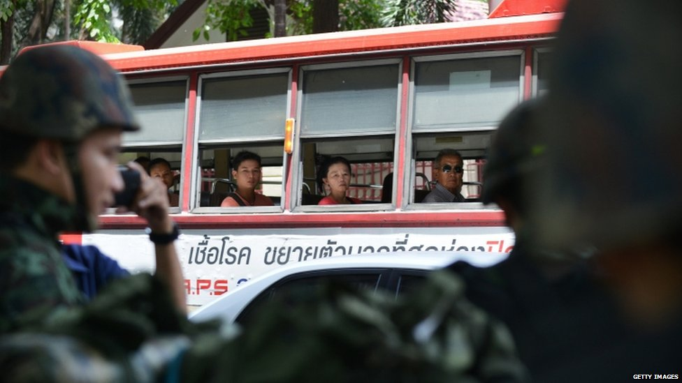 Commuters on a bus drive past soldiers in Bangkok (20 May 2014)