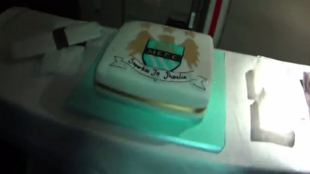 Manchester City present midfielder Yaya Toure a birthday cake as they fly to Abu Dhabi to celebrate winning the Premier League title.