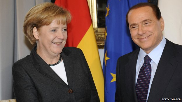 Silvio Berlusconi shakes hands with Angela Merkel during an Italy and Germany summit in Trieste in 2008