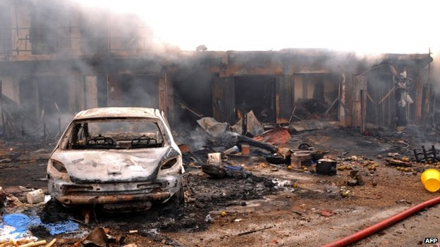 The wreckage of a charred vehicle remains in front of burning shops following a bomb blast at Terminus market in the central city of Jos (20 May 2014)