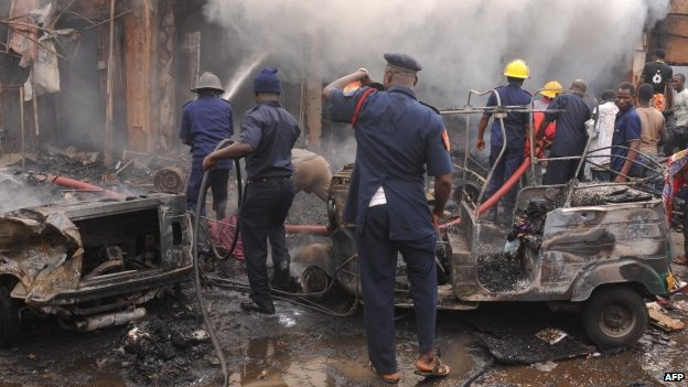 Firefighters extinguish a fire at the scene of a bomb blast at Terminus market in the central city of Jos (20 May 2014)