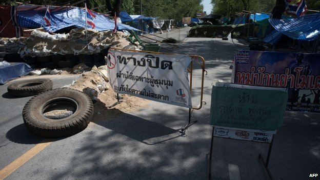 Barricades set up by anti-government protesters block a street outside government house in Bangkok on 21 May 2014