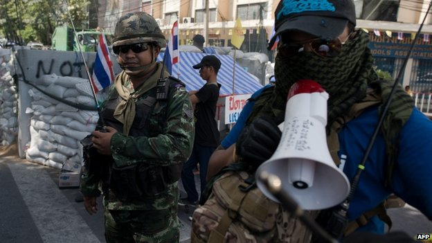 An anti-government protester (R) talks in a megaphone next to a Thai soldier (L) nearby government house in Bangkok on 21 May 2014