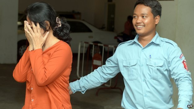 Taiwanese woman Lin Yu Shin (L) covers her face as she is escorted by a Cambodian prison guard (R) at the Phnom Penh Municipal court on 29 April, 2014
