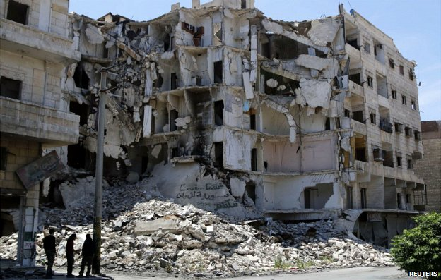 People stand along a damaged street in Bustan al-Basha district in Aleppo May 19, 2014