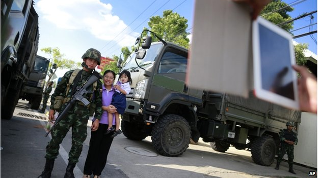 A Thai mother and daughter have their photograph taken with a soldier guarding the area near a pro-government demonstration site on the outskirts of Bangkok, Thailand, on 21 May.