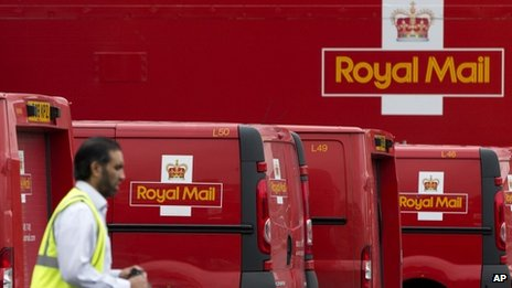 A Royal Mail worker walks past a group of delivery vans