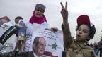 An Egyptian boy dressed in army clothes flashes the sign for victory as his mother holds a poster bearing an image of presidential candidate Abdul Fattah al-Sisi during a rally in Cairo, 20 May 2014