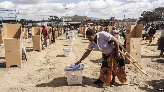 A Malawian woman casts her ballot as voting procedures resume on 21 May 2014 in Blantyre, Malawi