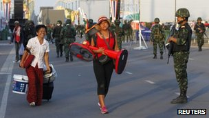 "Members of the pro-government ""red shirt"" group carry their belongings as they walk past Thai soldiers"