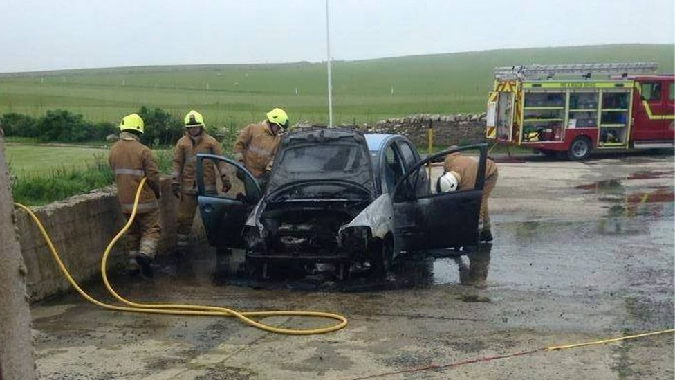 Firefighters at fire damaged car