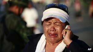 A pro-government demonstrator cries as she leaves the demonstration site after soldiers staged a coup Thursday, May 22