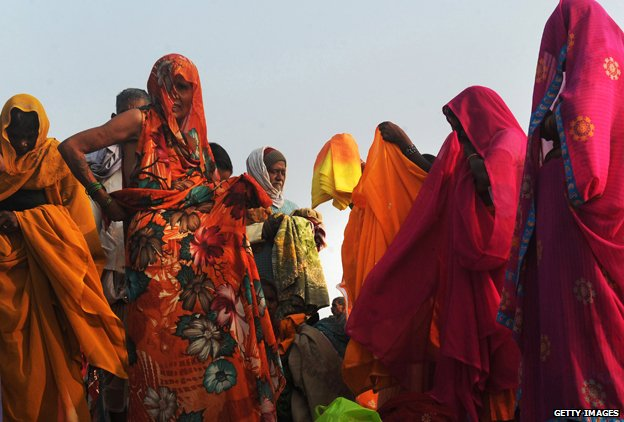 Indian Hindu pilgrims change their saris after taking a dip at the holy river
