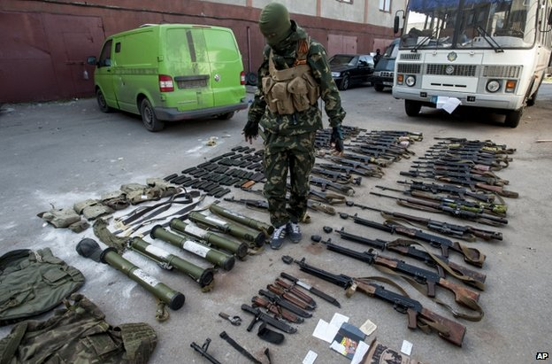 A pro-Russian gunman shows off weapons reportedly seized from Ukrainian soldiers, in the town of Horlivka, 22 May