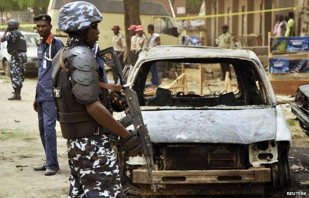 A policeman stands near damaged vehicles in Sabon Gari, Kano, Nigeria on 19 May  2014