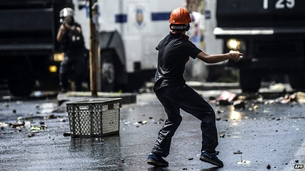 A young protester throws objects at Turkish riot police during clashes in Istanbul, Turkey - 22 May 2014