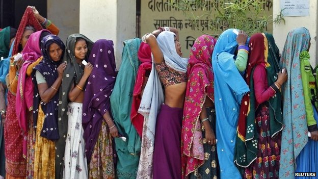 Women wait in a queue to cast their vote at polling station at Sirohi district in the desert Indian state of Rajasthan, April 17, 2014
