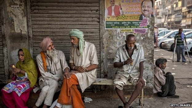 Indians drink tea under a poster showing Narendra Modi at a chai stall on May 21, 2014 in Delhi