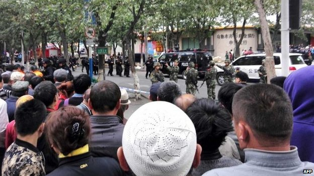 Residents gather to watch as police seal off the site where attackers ploughed two vehicles into a market and threw explosives, killing at least 31 people, in Urumqi in northwest China's Xinjiang region on 22 May 2014