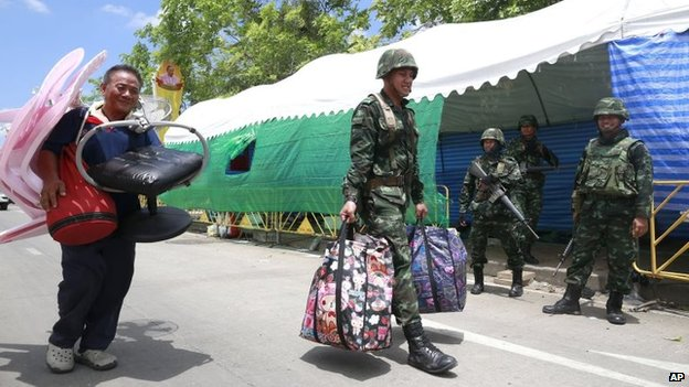 A Thai soldier carries belonging of a pro-government protester,