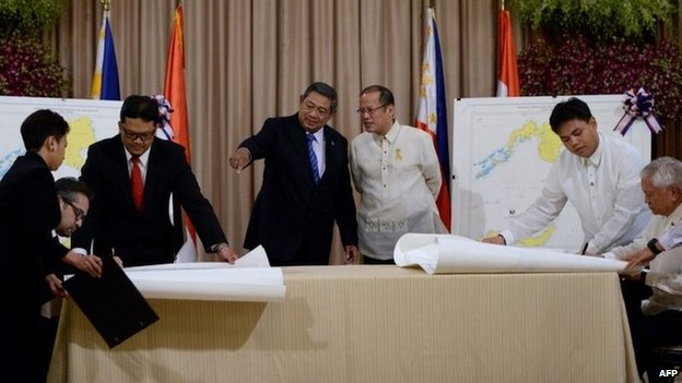 Philippine President Benigno Aquino (3nd R) stands beside Indonesian President Susilo Bambang Yudhoyono (4th R) as they look at Indonesian Foreign Minister Marty Natalegawa (2nd L) and Philippine Foreign Affairs Secretary Albert del Rosario (R) signing a maritime border accord at Malacanang Palace in Manila on 23 May 2014