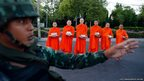 A Thai soldier stands guard while Buddhist monks beg for alms outside a temple near Government House in Bangkok