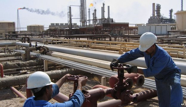 Iraqi workers operate the valves at the oil fields of Rumailah, Iraq, in August 2005