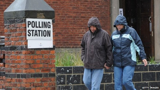 A couple walk past a polling station in Teesside