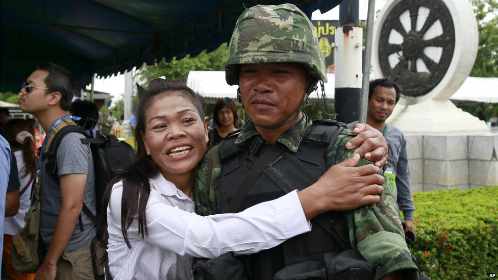 A pro-government demonstrator embraces a Thai soldier on the outskirts of Bangkok - 23 May 2014
