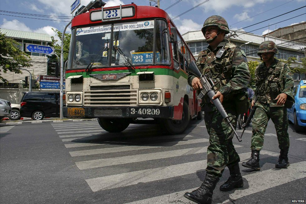 A bus passes Thai soldiers on patrol on a road near the Bangkok Army Club - 23 May 2014